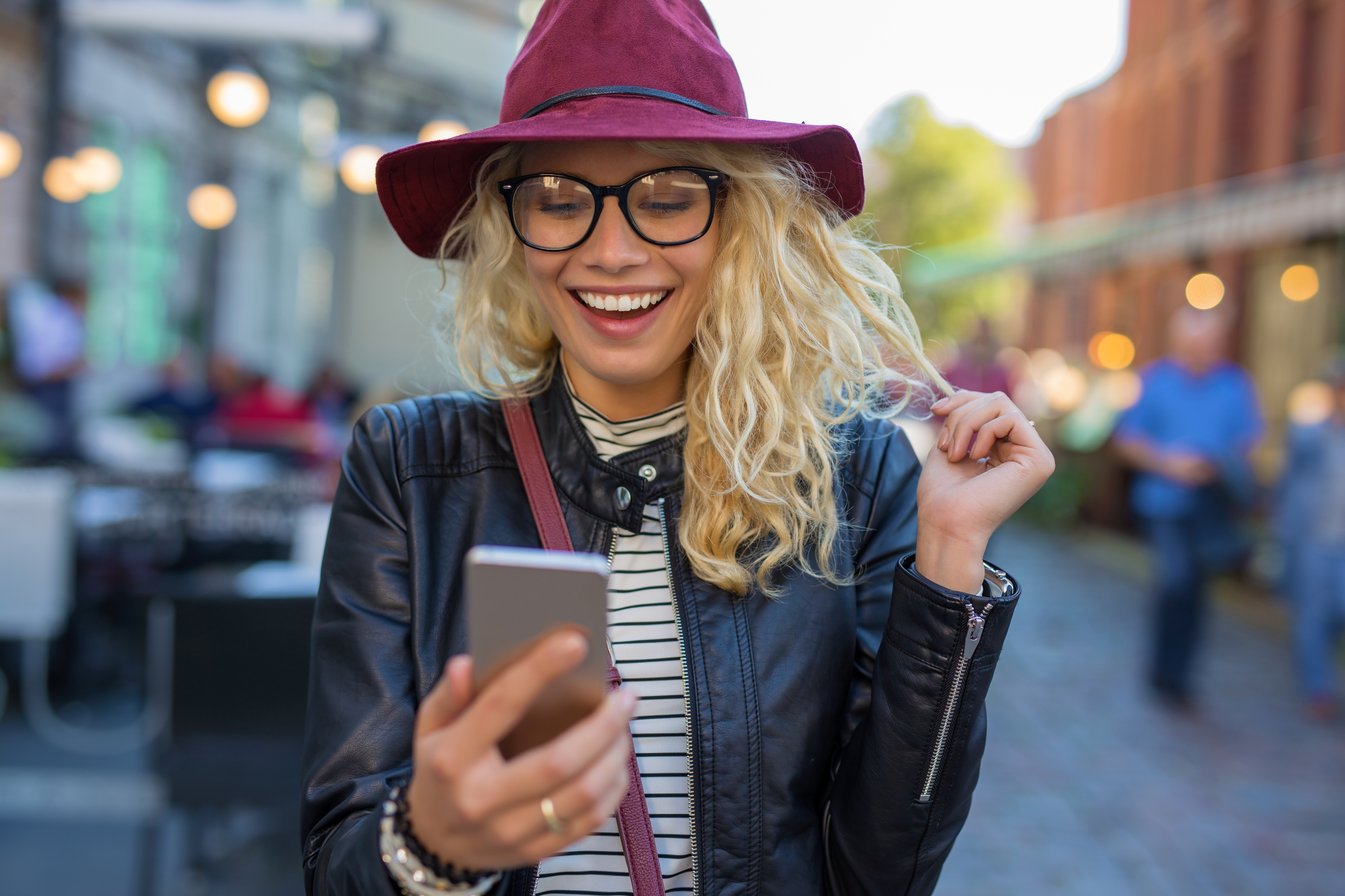 woman smiling at phone against city background