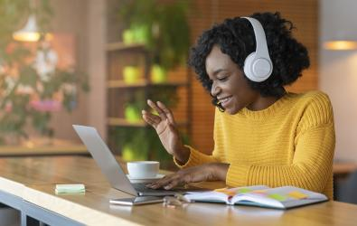 Woman wearing headphones and waving to laptop screen